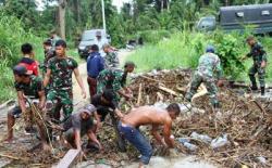 Prajurit Satgas Yonif 131/Brs dan Warga Bahu-membahu Bersihkan Material Sampah dan Lumpur