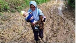 Rutinitas Seorang Guru Menggendong Bayinya Lewati Jalan yang Masih Tanah Berlumpur